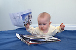 "Berkeley CA Baby six-months-old in ""airplane"" pose exploring magazine MR"