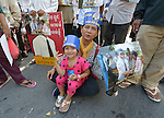 """A woman and her daughter participate in a vigil outside a Phnom Penh court on December 14, 2012, during a hearing in which judges denied an appeal by Mam Sonando, a Cambodian radio journalist and human rights activist. Mam Sonando was sentenced in October 2012 to 20 years in prison for """"insurrection,"""" despite local and international calls for his release."""