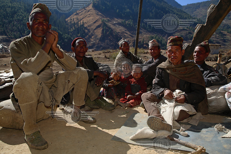 Group of men, one of whom makes a pair of trousers from home-spun wool.