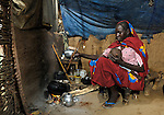 Fatna cooks a meal in her hut in a camp for internally displaced persons outside Kubum, in South Darfur, where humanitarian agencies are providing water, sanitation and other emergency services.