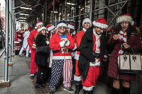 NEW YORK, NY - December 10: Revelers dressed as Santa Claus wait their turn to enter into a bar during the annual SantaCon event in New York City, December 10, 2016.VIEWpress/Maite H. Mateo
