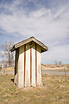 Pale yellow outhouse with witch on broom, crescent moon, rural Nevada