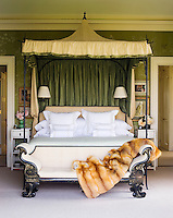 In the master bedroom, the wrought iron bed by Oscar de la Renta is fitted with a silk canopy and the bench is 19th century