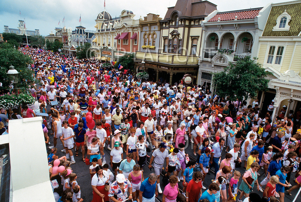 Orlando, Florida - Circa 1986. Crowds pile into Main Street at Disney World. Disney World is a world-renowned entertainment complex that opened October 1, 1971 in Lake Buena Vista, FL. Now known as the Walt Disney World Resort, the property covers 25,000 acres and has an annual attendance of 52.5million people.