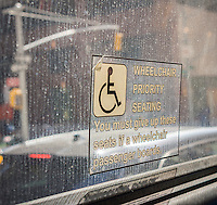 A priority seating sign reserving seats for individuals in wheelchairs is seen on a New York bus on Sunday, March 22, 2015.  (© Richard B. Levine)