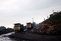 Dumpers carrying coal at Kujama mining area, Jharia. The area is badly affected by mine fire and people here work under great risk. A huge coal mine fire is engulfing the city of Jharia from all its sides. All scientific efforts have gone in vain to stop this raging fire. This fire is affecting lives of people living in and around Jharia. Jharkhand, India. Arindam Mukherjee