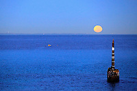 A cottesloe surf club member on an early morning paddle to catch the full moon setting over Rottnest Island.