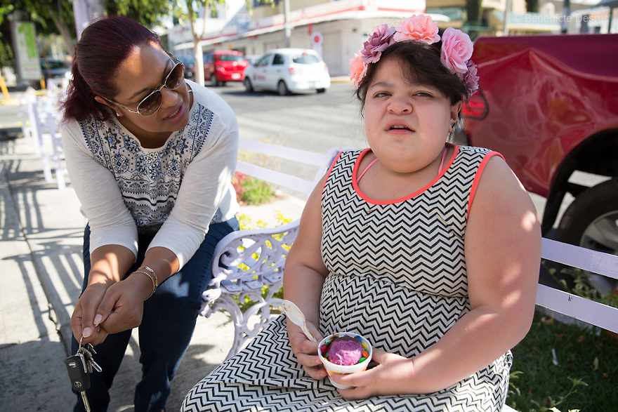 """Ana Ximena Navarro (R) and her aunt Gabriela Rios Ballesteros (L), eat an ice cream in Guadalajara, Mexico on February 22, 2017. Ximena was diagnosed as an infant with Hurler syndrome. Hurler syndrome is the most severe form of mucopolysaccharidosis type 1 (MPS1), a rare lysosomal storage disease, characterized by skeletal abnormalities, cognitive impairment, heart disease, respiratory problems, enlarged liver and spleen, characteristic facies and reduced life expectancy. Ximena was being given enzyme replacement therapy (ERT) when she was 19 months old, and she was suddenly able to eat and sleep. She is now 12, and has normal hormonal development for her age, although some mental delay, according to her father. """"Without the treatment, she would have died from all the complications — untreated, children have a very bad quality of life and typically die before they are seven"""", her father says. Photo credit: Bénédicte Desrus"""