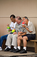 Three local men eating Matsumoto's Shave Ice outside their Haleiwa store on Oahu's North Shore, Hawaii