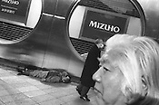 Homeless man sleeps on the pavement outside of a Mizhuo bank in Shinjuku, Tokyo, Japan. 2004