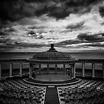 Early morning, cloudy in low light.  The Spa bandstand in Scarborough, a victorian seaside attraction which hosts daily live music.  Empty deckchairs await the first visitors of the day.