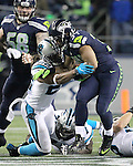 Seattle Seahawks running back Thomas Rawls (34) breaks the tackles of Carolina Panthers free safety Michael Griffin (22) and defensive tackle Kyle Love (77) on his way to a 13-yard gain in the third quarter at CenturyLink Field in Seattle, Washington on December 4, 2016.  Rawls ran for 105 yards on 16 carries and scored two touchdowns in the Seahawks 40-7 win over the Panthers.  ©2016. Jim Bryant photo. All Rights Reserved.