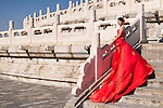 Young bride in red wedding dress in front of The Temple of Heaven in Beijing, China