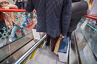 Shoppers with their purchases in shopping bags on an escalator in a store in New York on Sunday, December 6, 2015.  (© Richard B. Levine)