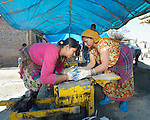 Amna Shrestha (left) and Sassawti Shrestha extract a cement block from a hand-operated press in Sanogoan, Nepal. They and their neighbors will use the blocks to build new homes following the April 2015 earthquake that ravaged the Newar community, destroying almost all the village's homes. The community has been helped by the ACT Alliance to rebuild. The ACT Alliance has provided  blankets, tents, and livelihood assistance, and is helping villagers form the tens of thousands of cement blocks they will need to construct permanent housing.