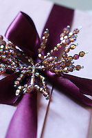 Close up of a Christmas present tied with purple ribbon and a beaded decoration