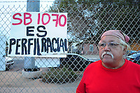 "Phoenix, Arizona. September 22, 2012 - Salvador Reza, long-time community organizer, Sheriff Arpaio's opponent and ""Festival of Resistance"" against Arizona's ""Show Me Your Papers"" law, takes a break next to a sign (written in Spanish) that read ""SB 1070 is racial Profiling."" Photo by Eduardo Barraza © 2012"