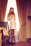 Beautiful sensual young woman in white night gown standing by the window