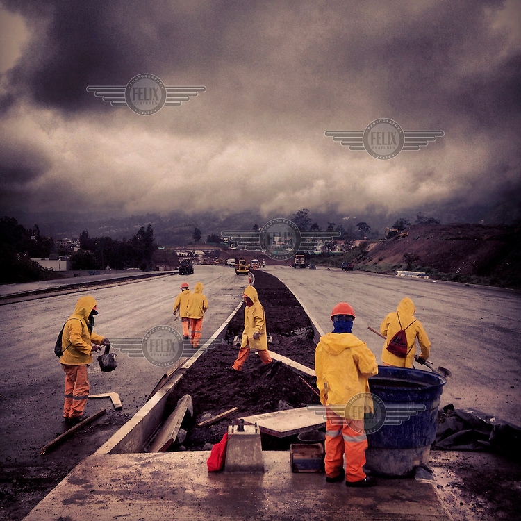 Workers building the superautopista (superhighway). Workers build the highway that now runs directly through Rumihuaico in Cumbaya, Ecuador, on December 19th, 2013.
