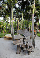 A group of wooden sculptural mushrooms 'growing' in a sandy palm grove in the tropical garden