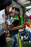 Native American , Chaske Hill Sicangu Lakota and Seneca , mother dressing and preparation as  her 3 year old son is looking in the mirror checking his face paint before the pow wow dance contest at the Thunderbird powwow in Queens, NY .