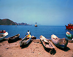 Old fishing boats beached on the sand with fishing trawler in the background, Santa Marta, Colombia. Circa 1975
