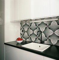 Graphic patterns, added to a simple palette of black and white create an elegant combination. In the kitchen a simple white enamel sink is set in the black work surface.