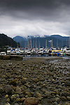 Low tide at Deep Cove Bay with clouds above the mountains over Mount Seymour provincial park. Deep Cove, Burrard Inlet, Vancouver, British Columbia, Canada.