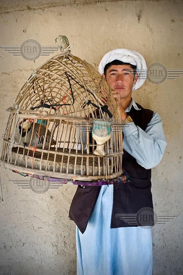 A bird keeper holds up a birdcage containing a mynah bird.