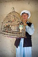 A bird keeper holds up a birdcage containing a mynah bird.