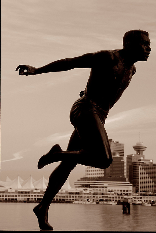 Statute of runner Harry Jerome in Stanley Park, with Vancouver skyline
