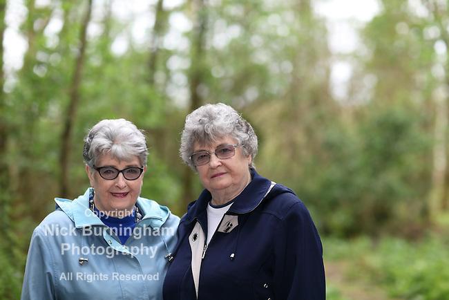 Elderly twin sisters walking in the woods - shallow depth of field
