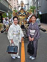 Two ladies in kimono`s pose infront of portable shrine at local festival,
