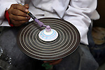 Africa, Morocco, Fes. Moroccan artisan hand paints ceramics on spinning wheel.