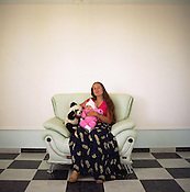 Garoafa, a young Roma woman, sits holding her friends baby in one of the rooms of her new home. the house has been built with the profits of scrap metal dealing by her family, and although furnished is not particularly lived in. Much of the furniture is bought as a symbol of their new wealth..