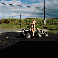 Austin Hoyt, 4, rides his toy tractor while supervised by his great grandfather Dick, age 69 in Ancramdale, NY.