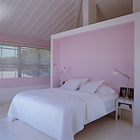 The soft pink walls of the bedroom are kept bare to encourage a sense of calm