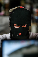 An online gamer dressed in balaclava while playing a game. One of the world's largest convention of computer enthusiasts, simply called 'The Gathering'. Over five thousand young people come together each Easter, some travelling long distances, each carrying their own computer equipment to the massive Vikingship sports hall in the city of Hamar. The main activity is online gaming. Many hardly see daylight or taste fresh air for the entire five days as they compete with their fellow geeks for cash prizes and the honour of being the best.