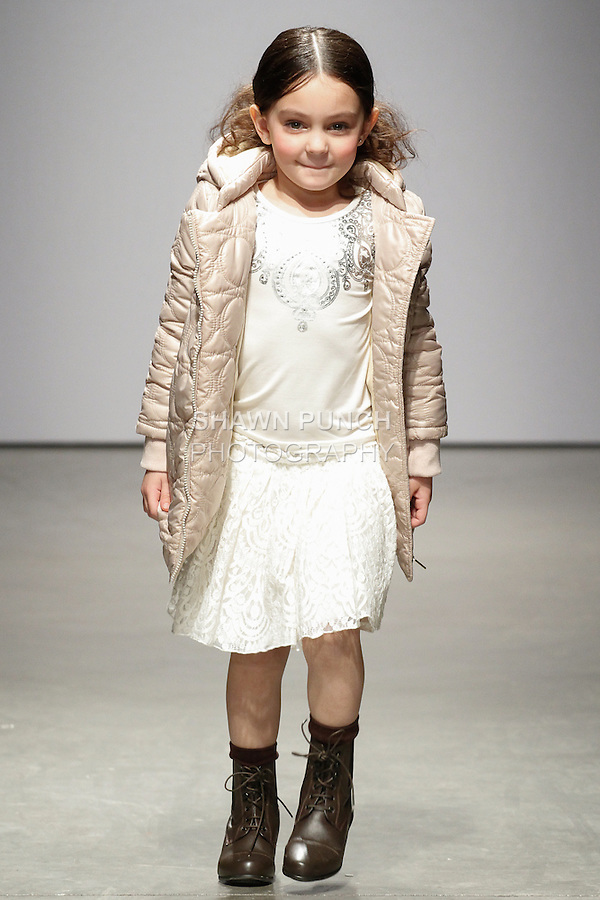 Young model walks runway in an outfit from the IMOGA Fall Winter 2014 collection by HeaJung Chung, at petitePARADE Fall 2014, during Kids Fashion Week in New York City, on March 8, 2014.