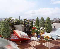 Small roof terrace with alternating wooden floor tiles between two skylights with a view over London