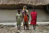Gita Sardar and her children standing in front of their hut at Sunderban. Gita Sardar is the widow of Subal Sardar who was killed by a tiger on 6th of April 2011. Sunderban, West Bengal, India. Gita now works as a daily waged labour and earns about a dollar a day. Moreover she do not get the job everyday.  Sunderban, West Bangal, India. April 2011. Arindam Mukherjee