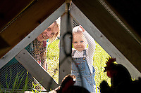 A mother and young son check on their chicken flock in a chicken coop on their farm.