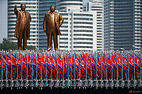 People carry flags in front of statues of North Korea founder Kim Il Sung (L) and late leader Kim Jong Il during a military parade marking the 105th birth anniversary Kim Il Sung in Pyongyang, April 15, 2017.    REUTERS/Damir Sagolj