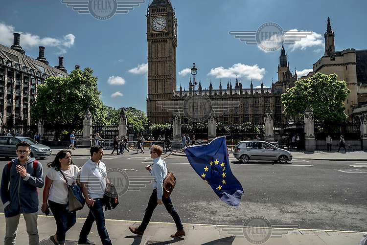 A man carrying an EU flag walks past the Houses of Parliament on the morning following the EU referendum, by which time it was clear that the country had voted to leave the EU.