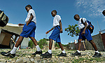 Students arrive at the Notre Dame de Petits school at the beginning of a school day in Port-au-Prince, Haiti. The school's building collapsed in the January 2010 earthquake, and while some classes are conducted in the ruins, other classes meet in large tents provided by International Orthodox Christian Charities.
