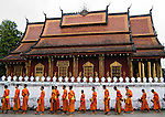 Buddhist monks walking the streets of Luang Prabang past Wat Seng early in the morning collecting alms.