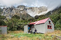 Trampers enjoying meal at Douglas Rock Hut in Copland Valley under Southern Alps, Westland National Park, West Coast, South Westland, World Heritage Area, New Zealand