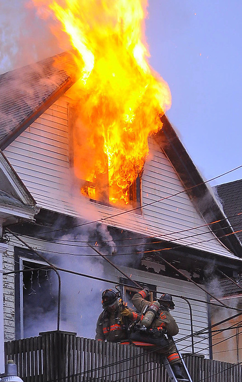 Buffalo Firefighters operate off of a ground ladder as heavy fire vents from the attic area of a 2.5 wood frame dwelling. Firefighters were ordered off the attic area by the Division Chief, one person was rescued during this fire, which started as a auto fire between an occupied and vacant house