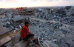 A Palestinian man sits on the rubble of his destroyed house after returning home in the Tufah neighbourhood in eastern Gaza City on August 31, 2014. Calm returned to the coastal enclave in a August 26 ceasefire, and Gazans were gradually starting to rebuild their lives after a bloody and destructive 50-day war, the deadliest for years. Photo by Ashraf Amra