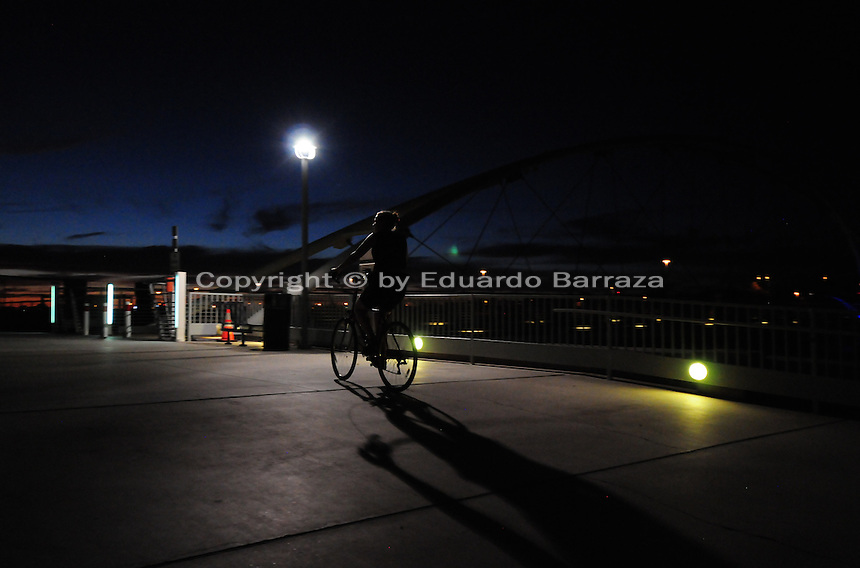 Tempe, Arizona. A lady on a bike enjoys the cooler evening weather next to Tempe Town Lake. The artificial lake is a reservoir on a segment of the currently dry riverbed of the Salt River. The new dam will be a cost-effective solution expected to last for decades. The construction is called Town Lake Western Dam Replacement Project. Photo by Eduardo Barraza © 2015